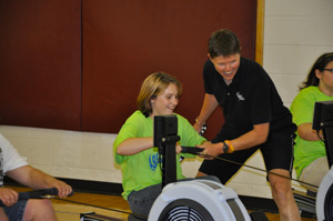 Terry Smythe helps a Special Olympian with indoor rowing at the Michigan Summer Games