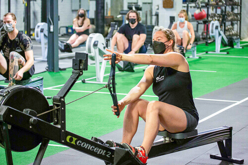 A rowing coach shows her students the best hand position for rowing on a rowing machine